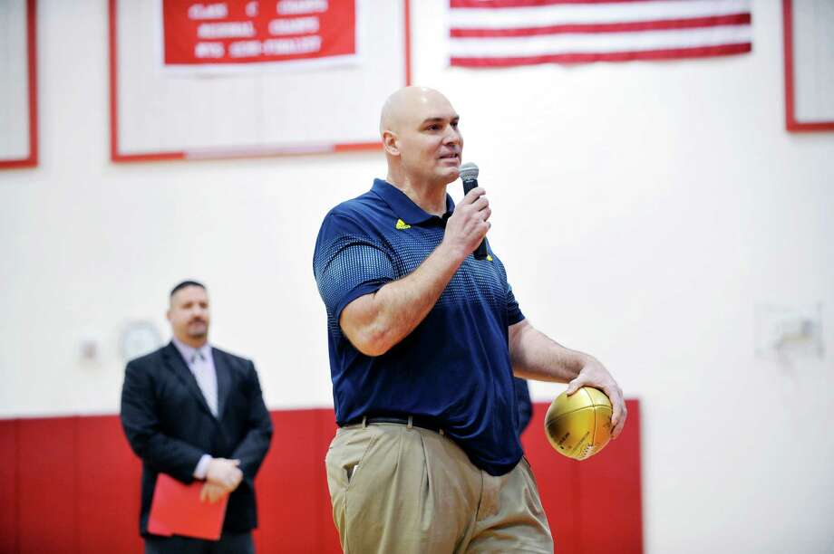 """Mechanicville High School alumnus Joe Cocozzo holds an NFL commemorative golden football as he speaks to students during a presentation of the football honoring Cocozzo's accomplishments on the field, in the classroom and in the community on Tuesday, Feb. 9, 2016, in Mechanicville, N.Y.  Cocozzo played for the San Diego Chargers from 1993 to 1997 and played in the Super Bowl for the team.  Mechanicville High School fall sports students were also awarded their Scholar Athlete Team Awards during the event.  For teams to attain Scholar Athlete awards the team GPA average must be 90 or above.  The NFL as part of its """"On the Fifty"""" campaign to commemorate the 50th anniversary of the Super Bowl, is gifting celebratory gold footballs to the high school of every player and head coach who has appeared in a Super Bowl.   (Paul Buckowski / Times Union) Photo: PAUL BUCKOWSKI / 10035340A"""