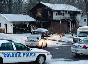 Police remain at the scene of a fatal fire on Schalren Drive, Colonie, that is presumed to have killed town police Officer Israel J. Roman, as well as his wife and younger son. (Skip Dickstein / Times Union)
