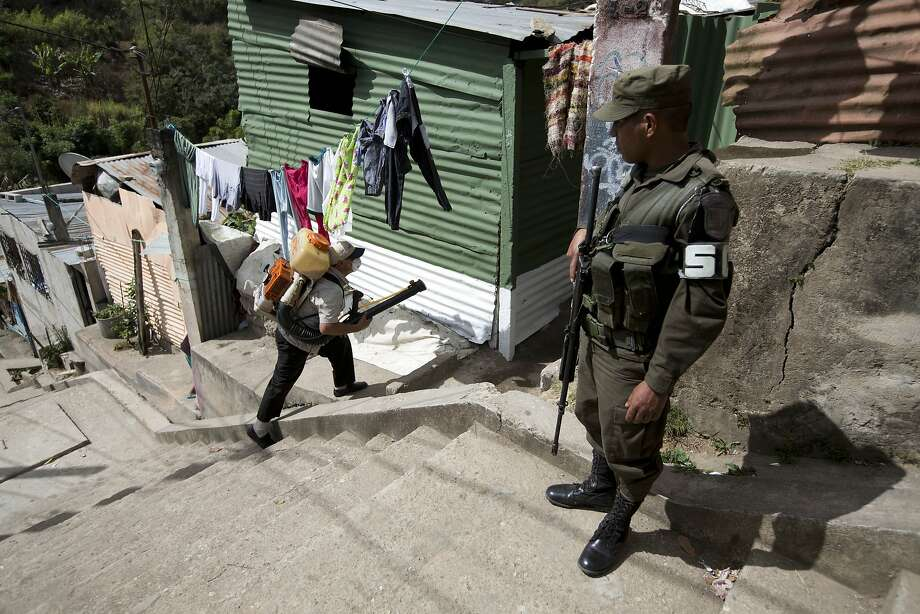 A soldier provides security for a health worker fumigating against the Aedes aegypti mosquito in Guatemala City. Gangsters who control the streets sometimes threaten the workers' lives. Photo: Moises Castillo, Associated Press
