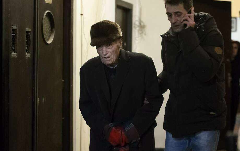Former prison commander Alexandru Visinescu leaves his Bucharest home escorted by a plainclothes police officer. Photo: Andreea Alexandru, Associated Press