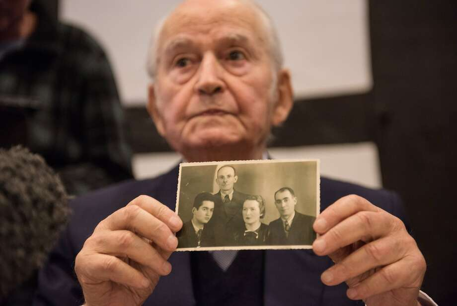 Auschwitz concentration camp survivor Leon Schwarzbaum presents an old photograph showing himself, left, next to his uncle and parents, who all died in Auschwitz. Photo: Bernd Thissen, Associated Press