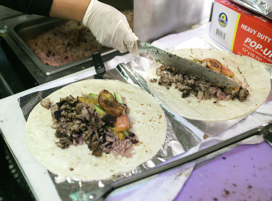Scotch Bonnet's Jamaican-style burritos with pork, vegetables and plantains, left, and the more traditional baked beef patties, right. The burritos have become the truck's best-sellers. / ONLINE_YES