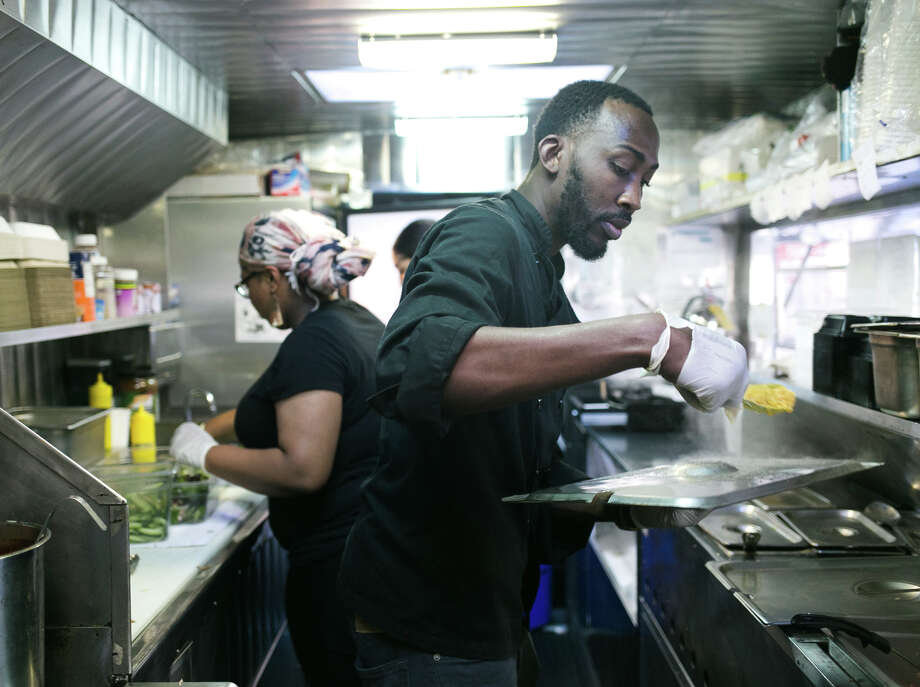 Scotch Bonnet food truck owner O'Brian Matterson, with Maritza Butler in the FiDi, brings Jamaican food to the Bay Area with jerk chicken and pork — and a goat curry burrito. / ONLINE_YES