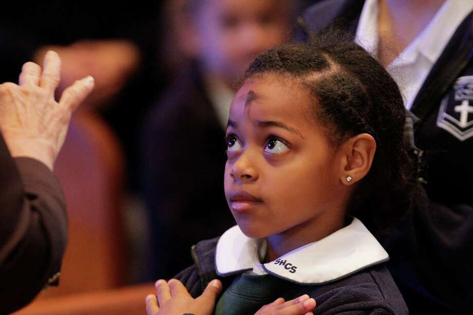 """St. Helen Catholic Church School first-grader Noelle Reed receives ashes during the Ash Wednesday Mass Feb. 10, 2016, in Pearland.  Catholics will mark the beginning of Lent with Ash Wednesday. Throughout the day, thousands will attend Masses and Services during which they will receive ashes across their foreheads in a ceremony known as the """"imposition"""" of ashes. The ashes symbolize penance and are a reminder of our mortality. Lent is the 40-day liturgical season during which Catholics prepare for the celebration of the resurrection of Christ on Easter Sunday. The preparation includes fasting, prayer and works of charity. Photo: Steve Gonzales, Houston Chronicle / © 2016 Houston Chronicle"""