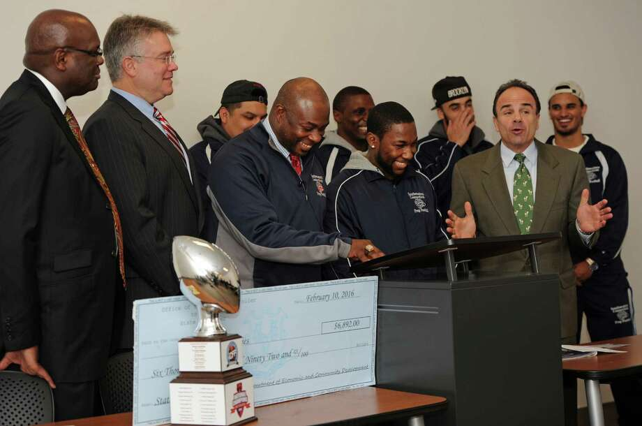Mayor Joe Ganim, right, talks about his football playing days during a check presentation to the Southwestern Connecticut Grizzlies Football team at Housatonic Community College on Wednesday, Feb.10, 2016 in Bridgeport, Conn. State Rep. John Shaban, R-Redding, second from left,  presented a check for nearly $7,000 to Grizzlies coach Bernie Armstrong and player Jacqua Solomon, center. Photo: Cathy Zuraw, Hearst Connecticut Media / Connecticut Post