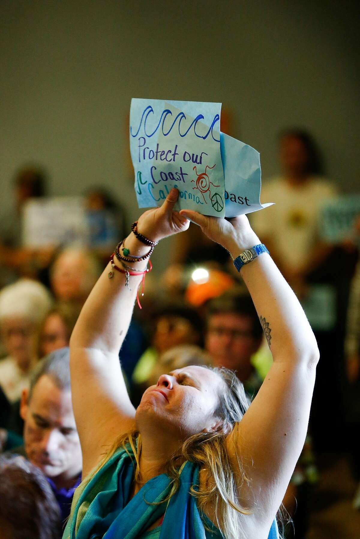 Genoa Robertson reacts as California Coastal Commission Charles Lester speaks at the Morro Bay Community Center in Morro Bay , Calif. on Wednesday, February 10, 2016. The proposal to fire California Coastal Commission Executive Director Charles Lester has set off furor throughout the state.
