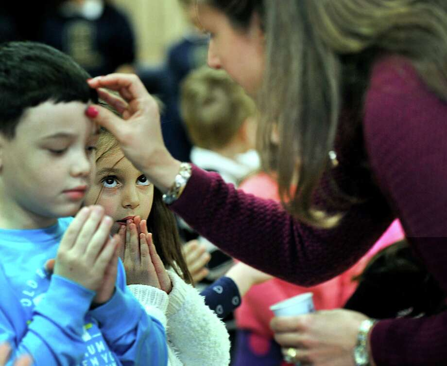 Haylee Palmer, pays close attention, as teacher assistant and Eucharistic Minister Janette Buonaiuto places ashes on Isaac Leone's forehead. The children, kindergartners at St. Gregory the Great Catholic School in Danbury, observe Ash Wednesday with an all-school assembly Wednesday, Feb. 10, 2016. Photo: Carol Kaliff / Hearst Connecticut Media / The News-Times