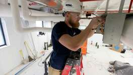 Apprentice Erik McKenna works on installing a ventilation system in Oak Creek, Wis. McKenna, a fourth-year sheet metal apprentice who served two tours in Afghanistan in the Army, works for Total Mechanical Inc.