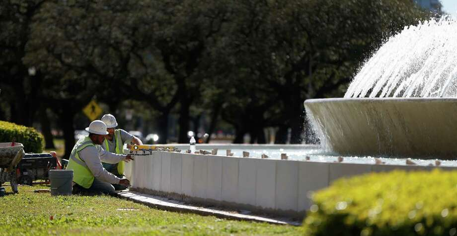 Workers place stones around the Mecom Fountain at the traffic circle at Main and Montrose,  Wednesday, Feb. 10, 2016. Photo: Karen Warren, Houston Chronicle / © 2015  Houston Chronicle