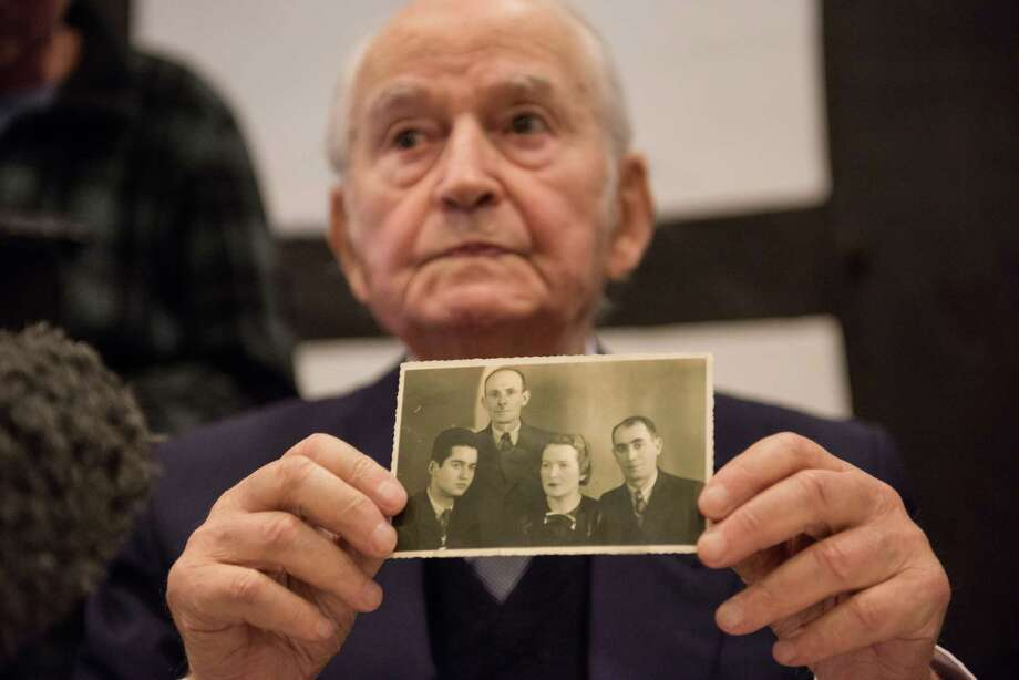The first Auschwitz survivor slated to testify is Leon Schwarz- baum — who, like the defendant, is 94. Here he shows a photo of himself, left, next to his uncle and parents, who all died. Photo: Bernd Thissen / Associated Press / dpa