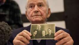 The first Auschwitz survivor slated to testify is Leon Schwarz- baum — who, like the defendant, is 94. Here he shows a photo of himself, left, next to his uncle and parents, who all died.