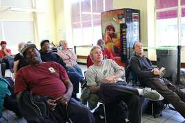 (l-r) Keith Wilkerson, Jeff Forehand and Jim Harding watch the Super Bowl at the Multi Service Center South, which is one of the largest homeless shelters in San Francisco, California on Sunday, February 7, 2016.