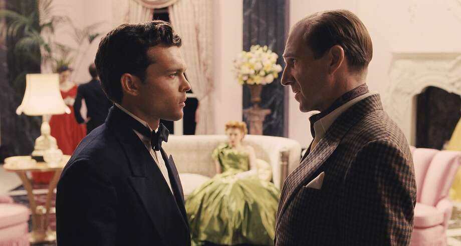"In this image provided by Universal Pictures, Alden Ehrenreich, left, as rising star Hobie Doyle speaks with Ralph Fiennes as director Laurence Laurentz in ""Hail, Caesar!,"" a comedy from filmmakers Joel and Ethan Coen. The movie opens Friday, Feb. 5, 2016. (Universal Pictures via AP) Photo: Universal Pictures, Associated Press"