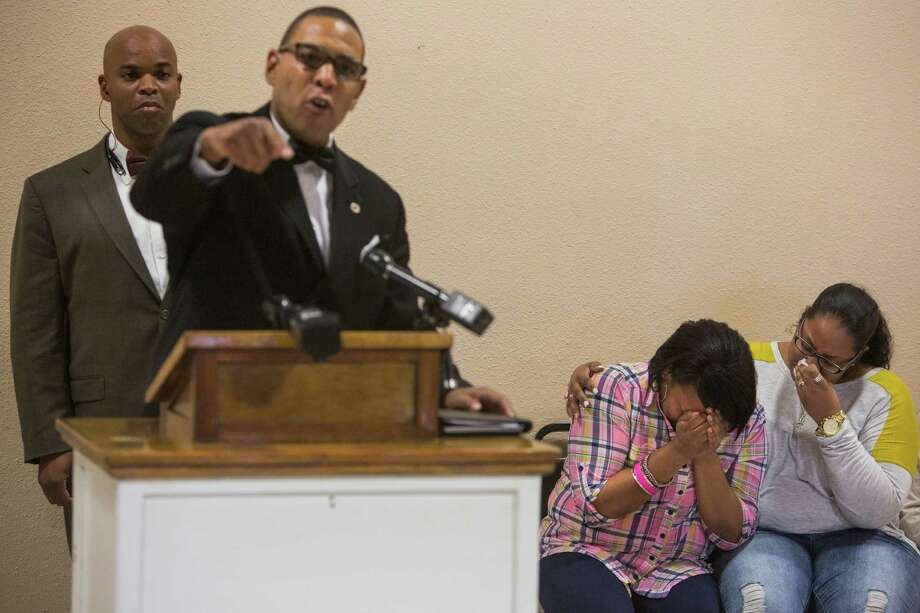 Terrence Coklow of the Greater East Side Coalition speaks while Charissa Sprawling-Mickles, right, comforts her sister Elena Sprawling-Scott during a press conference held at the Barbara Jordan Community Center about Antronie Scott's death in San Antonio, Texas on February 6, 2016.  Scott, who was unarmed, was shot and killed by a San Antonio police officer outside of his car on Thursday evening as his wife Elena Sprawling-Scott watched from the passenger seat. Photo: Carolyn Van Houten / Carolyn Van Houten / 2016 San Antonio Express-News