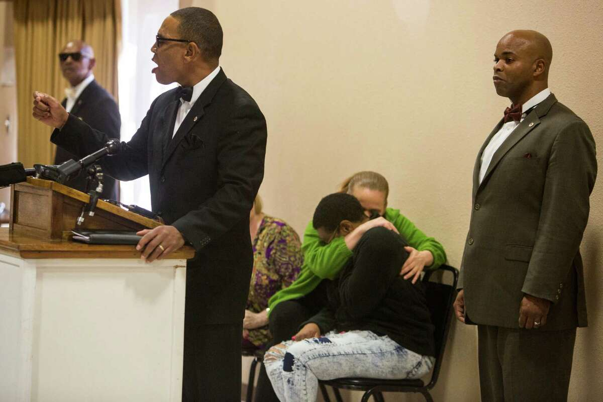 Terrence Coklow of the Greater East Side Coalition speaks while Kacie Herrick comforts Diane Peppar during a press conference held at the Barbara Jordan Community Center about Antronie Scott's death in San Antonio, Texas on February 6, 2016. Herrick is Scott's stepsister and Peppar is Scott's mother. Scott, who was unarmed, was shot and killed by a San Antonio police officer outside of his car on Thursday evening as his wife watched from the passenger seat.