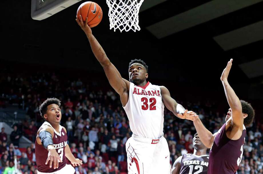 Alabama guard Retin Obasohan, center, scores against Texas A&M guard Admon Gilder, left, and center Tyler Davis, right, during the second half of an NCAA college basketball game, Wednesday, Feb. 10, 2016, in Tuscaloosa, Ala. Alabama won 63-62. (AP Photo/Brynn Anderson) ORG XMIT: ALBA112 Photo: Brynn Anderson / AP