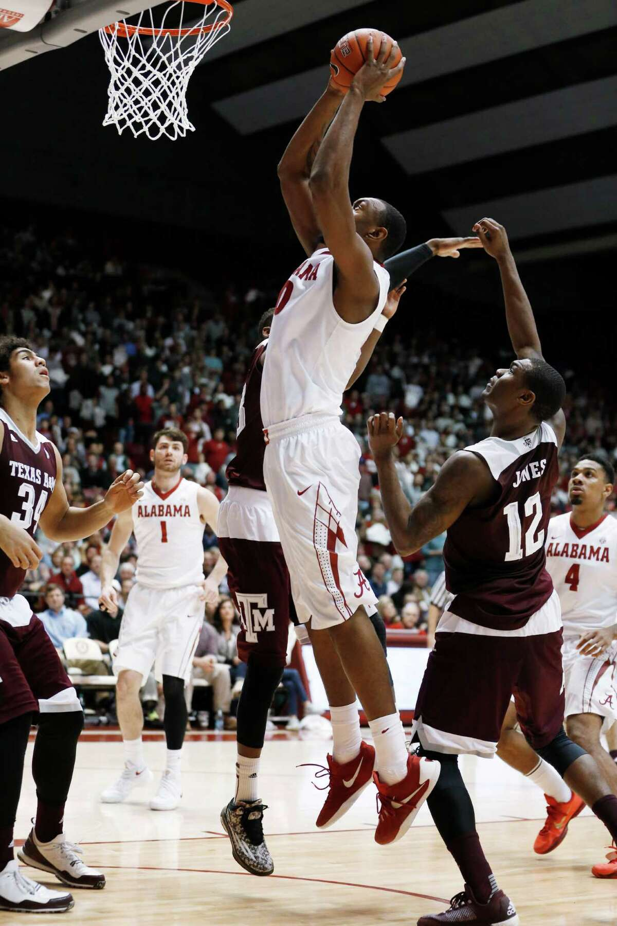 Alabama forward Jimmie Taylor (10) shoots and scores in front of Texas A&M guard Jalen Jones (12) during the second half of an NCAA college basketball game Wednesday, Feb. 10, 2016, in Tuscaloosa, Ala. Alabama won 63-62. (AP Photo/Brynn Anderson)
