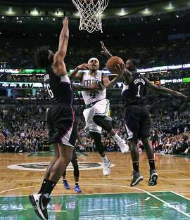 Boston Celtics guard Isaiah Thomas threads between Los Angeles Clippers forward Lance Stephenson (1) and center DeAndre Jordan, left, on a drive to the basket during overtime of an NBA basketball game in Boston, Wednesday, Feb. 10, 2016. Thomas scored 36 points as the Celtics defeated the Clippers 139-134. (AP Photo/Charles Krupa)