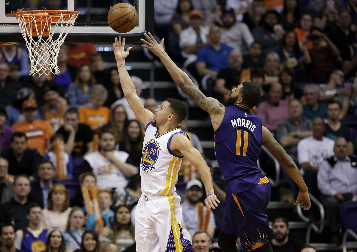 Golden State Warriors' Stephen Curry scores against Phoenix Suns' Markieff Morris (11) during the second half of an NBA basketball game, Wednesday, Feb. 10, 2016, in Phoenix. (AP Photo/Matt York)