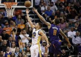 Golden State Warriors' Stephen Curry scores against Phoenix Suns' Markieff Morris (11) during the second half of an NBA basketball game, Wednesday, Feb. 10, 2016, in Phoenix. (AP Photo/Matt York)