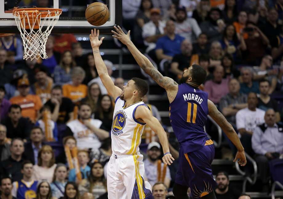 The Warriors' Stephen Curry scores against the Suns' Markieff Morris (11) during the second half of the Warriors' 48th win this season. Photo: Matt York, Associated Press