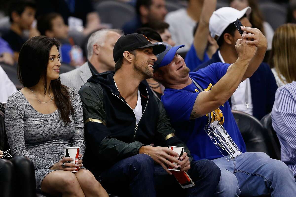 U.S. Olympic swimmer Michael Phelps poses for a selfie with a fan as he attends the NBA game between the Phoenix Suns and the Golden State Warriors at Talking Stick Resort Arena on February 10, 2016 in Phoenix, Arizona. The Warriors defeated the Suns 112-104.