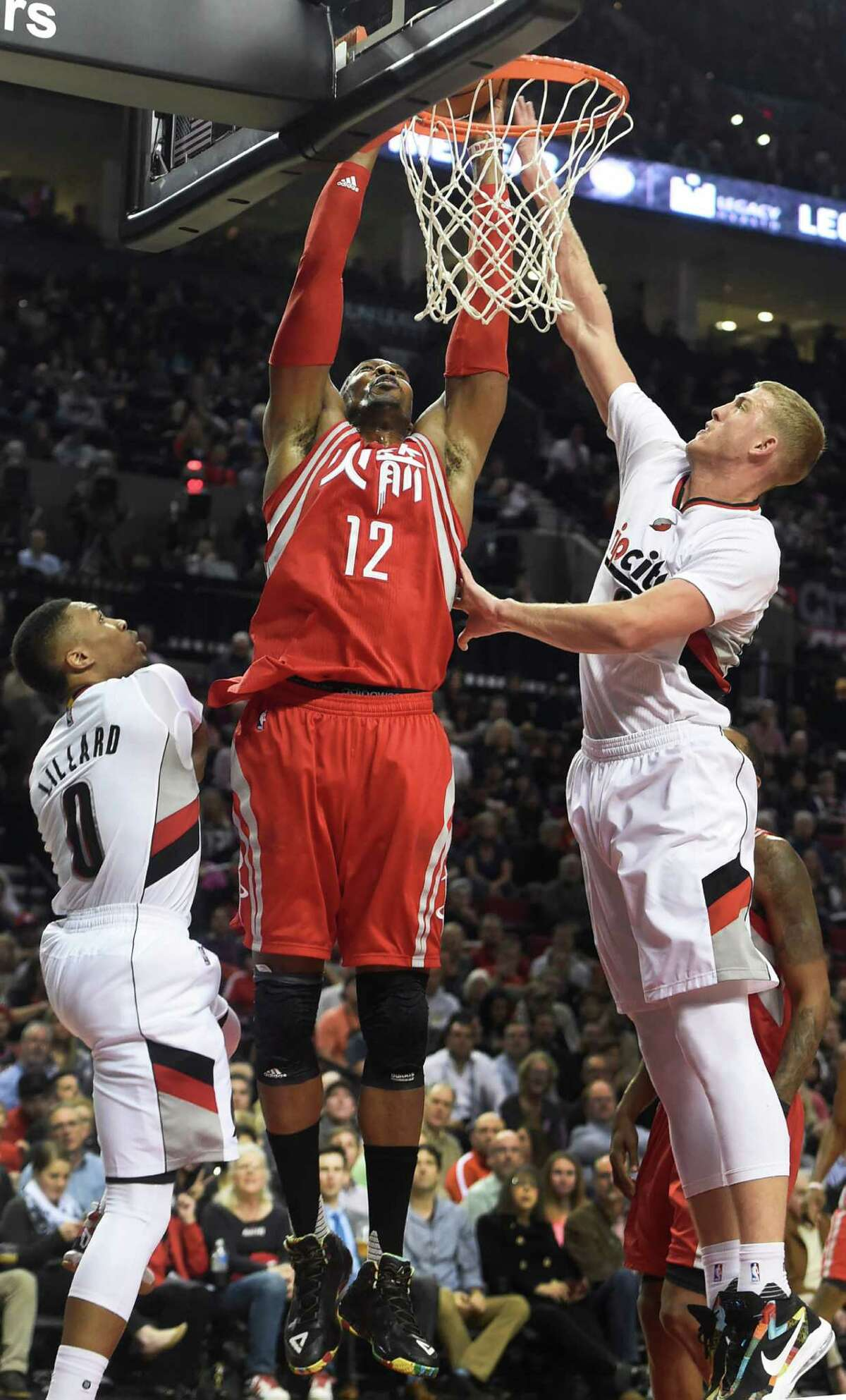Houston Rockets center Dwight Howard (12) goes up for a shot on Portland Trail Blazers guard Damian Lillard (0) and center Mason Plumlee (24) during the first half of an NBA basketball game in Portland, Ore., Wednesday, Feb. 10, 2016. (AP Photo/Steve Dykes)