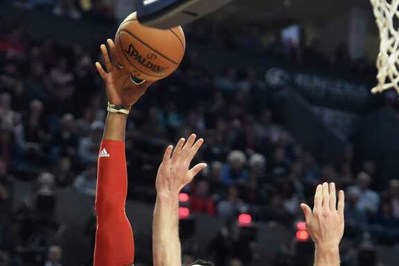 Rockets center Dwight Howard, left, shoots over the Blazers' Mason Plumlee during HoOward's 28-point game Wednesday night.