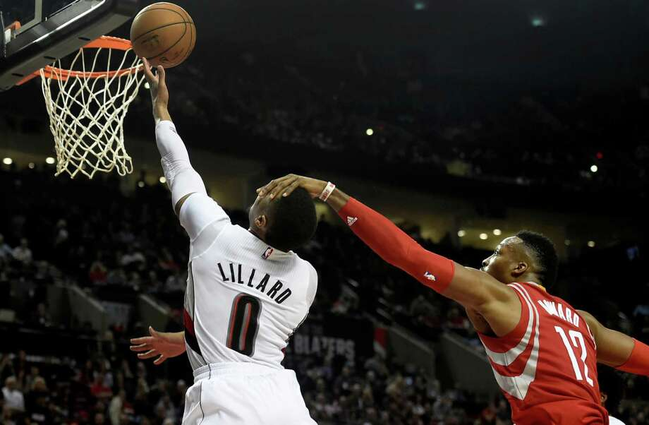 Portland Trail Blazers guard Damian Lillard (0) is fouled by Houston Rockets center Dwight Howard (12) as he drives to the basket during the second half of an NBA basketball game in Portland, Ore., Wednesday, Feb. 10, 2016. The Blazers won the game 116-103. (AP Photo/Steve Dykes) Photo: Steve Dykes, Associated Press / FR155163 AP
