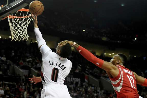 Portland Trail Blazers guard Damian Lillard (0) is fouled by Houston Rockets center Dwight Howard (12) as he drives to the basket during the second half of an NBA basketball game in Portland, Ore., Wednesday, Feb. 10, 2016. The Blazers won the game 116-103. (AP Photo/Steve Dykes)