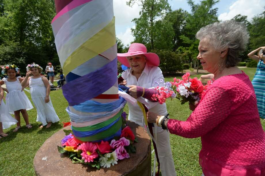 "Marty Craig (left) and Randy Hammerling secure the ribbons during the inaugural Maypole Festival held at Beaumont Botanical Gardens Saturday. The pole was erected in memory of Paula Marie Salter, aka ""Torchy,"" who was an active member of the community and remembered by friends for her bright and giving spirit. The tradition of the springtime maypole dance dates back to 14th century Europe. Photo taken Thursday, May 14, 2015 Kim Brent/The Enterprise Photo: Kim Brent/The Enterprise"