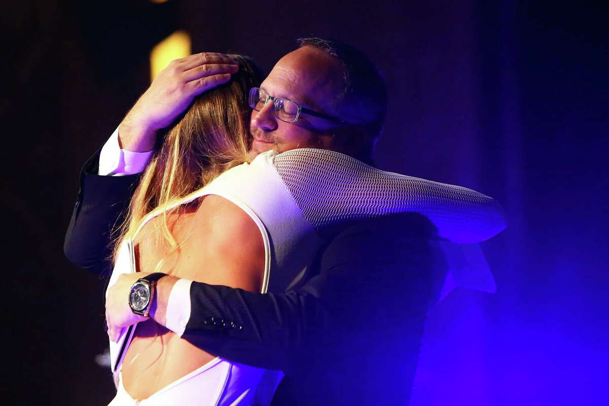 University of Washington women's basketball coach Mike Neighbors hugs player Katie Collier while presenting her with the Wayne Gittinger Inspirational Award during the 2016 MTRWestern Sports Star of the Year Awards, Wednesday, Feb. 10, 2016 at the Paramount Theater. Now the UW's starting center, Collier played basketball her senior year at Seattle Christian High School while undergoing chemotherapy for leukemia and made All-American.