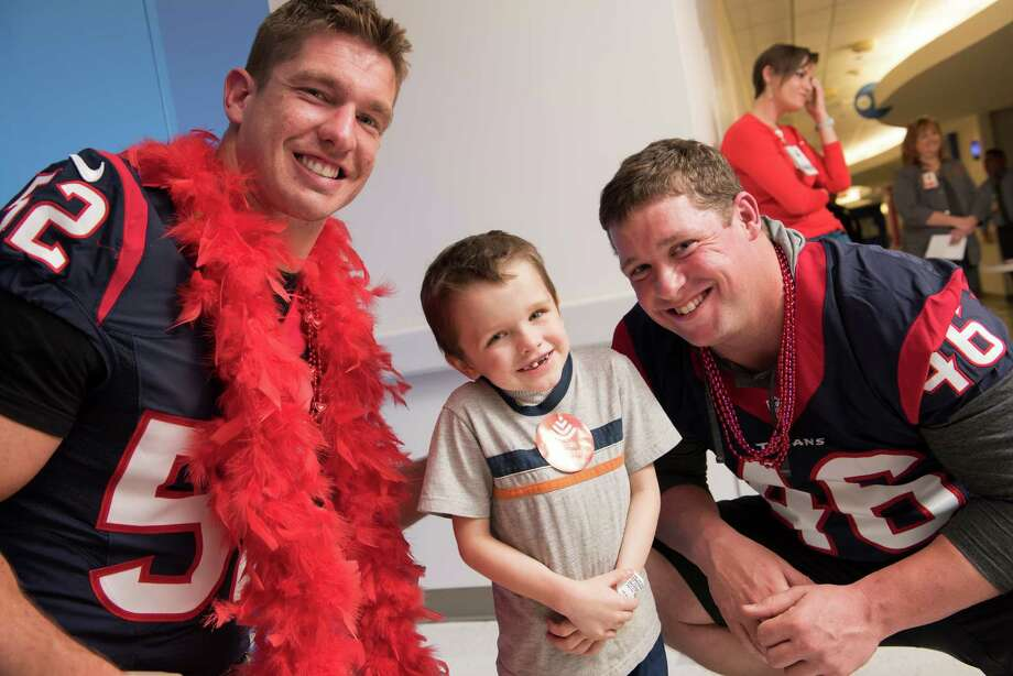Houston Texans linebacker Brian Peters and long snapper Jon Weeks made a heart patient smile during a visit to Texas Children's. Photo: PAUL VINCENT KUNTZ, Texas Children's Hospital / Texas Children's Hospital