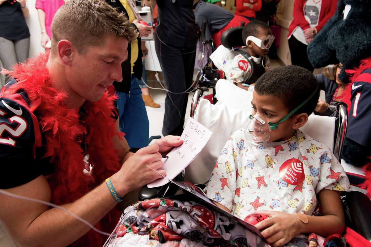 Houston Texans linebacker Brian Peters helps a young patient make a valentine.