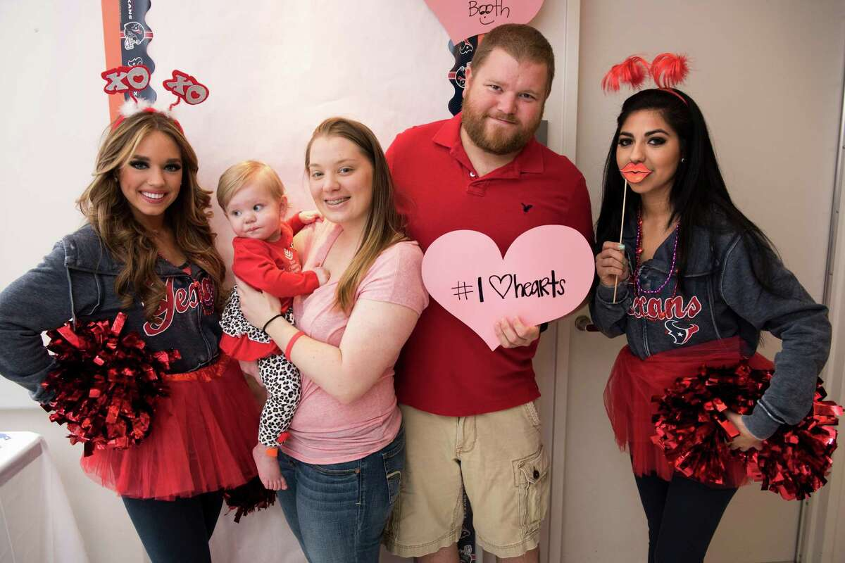 Houston Texans cheerleaders Krystal and Sarah M. pose with a Texas Children's patient family in the photo booth.