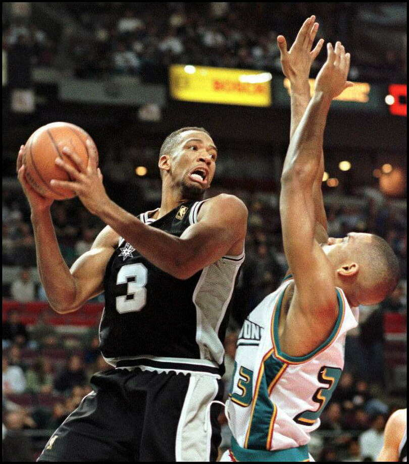 The San Antonio Spurs' Monty Williams (L) looks for someone to pass the ball to as he runs into the Detroit Pistons' Grant Hill (R) under the basket in the first quarter 10 January at the Palace in Auburn Hills, MI. Photo: MATT CAMPBELL, Getty Images / AFP