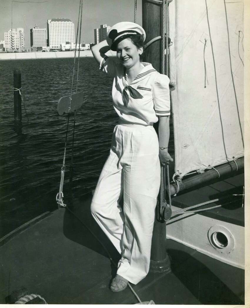 Corinne Putman reclines against the mast of a sailing craft in Corpus Christi with the skyline of the city in the background, ca 1939.