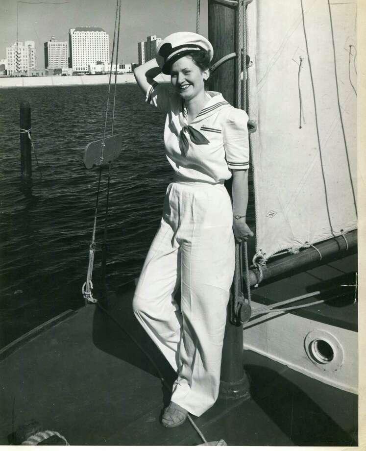 Corinne Putman reclines against the mast of a sailing craft in Corpus Christi with the skyline of the city in the background, ca 1939. Photo: File Photo