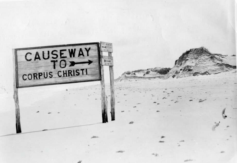 "Photographed in November 1935, the caption reads: ""Across this sandy stretch probably will be constructed the road connecting the padre island beach with the causeway to be built across Laguna Madre to Flour Bluff, 15 miles south of Corpus Christi. The sign pictured here directed traffic over the old Don Patricio causeway, destroyed three years ago by high water."" Photo: File Photo"