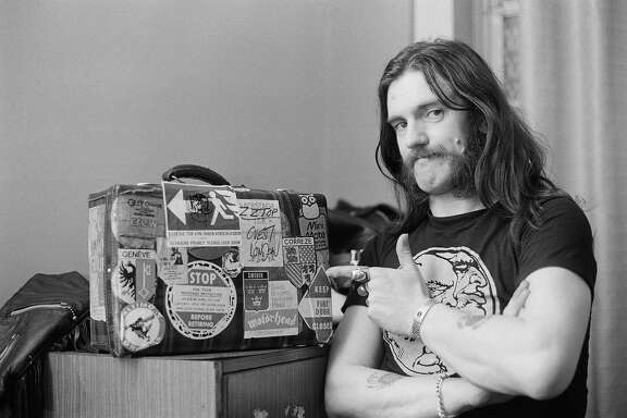 FILE: Motorhead Frontman Lemmy  Dies At 70 NEWCASTLE, ENGLAND - 22nd MARCH: Lemmy Kilmister from Motorhead points to a tour case backstage at City Hall in Newcastle, England on March 22nd 1982. (Photo by Fin Costello/Redferns)