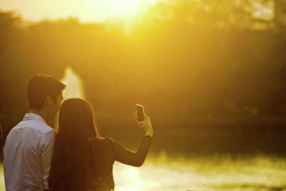 A young couple takes a photograph with a mobile phone during the last sunset of 2015 in Yangon on December 31, 2015.  AFP PHOTO / Ye Aung THU / AFP / Ye Aung Thu        (Photo credit should read YE AUNG THU/AFP/Getty Images) Photo: YE AUNG THU / YE AUNG THU / AFP/Getty Images / AFP