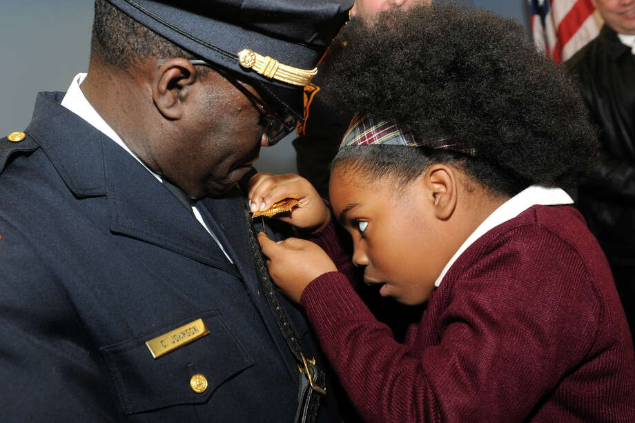 Daiajade Johnson, 9, works to pin a new LieutenantâÄôs Shield onto the uniform of her father, Bridgeport Police Officer Charles Johnson, during a promotion ceremony at the Morton Government Center, in Bridgeport, Conn. Feb. 11, 2016. Johnson and fellow officer Robert Magnuson were both promoted to the rank of Lieutenant Thursday. Photo: Ned Gerard, Hearst Connecticut Media / Connecticut Post