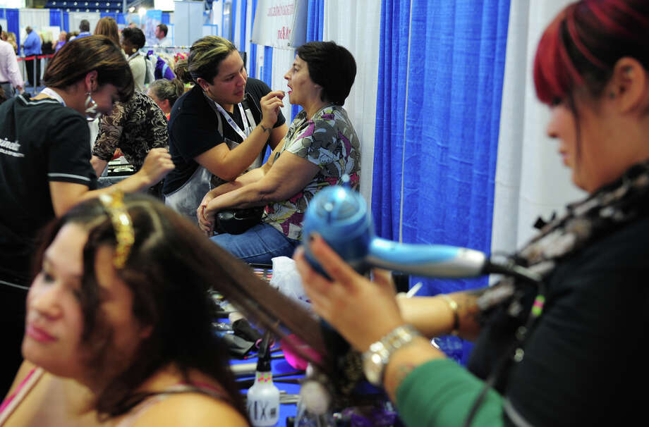 Pedro Lazo, a student at Marinello Beauty School in Fairfield, applies lipstick to Beverly Kennedy, of Seymour, at St. Vincent's Southern Connecticut Women's Expo held at the Webster Bank Arena in Bridgeport, Conn., on Saturday Sept. 27, 2014. The event attracts thousands of women looking to shop for the latest products and services in fashion, beauty, health, wellness, education and much more. Attendees will get to experience free health screenings, including mammograms along with health & wellness related discussions provided by St. VincentâÄôs physicians. Photo: Christian Abraham / Christian Abraham / Connecticut Post