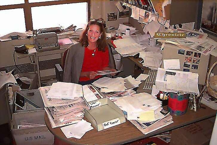 Carole Vernier at her desk outside Herb Caen's  office in 1995.
