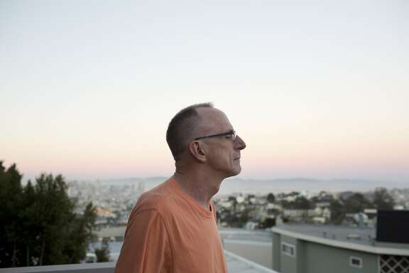 Kevin VandenBergh, a long-term AIDS survivor, looks at the city from the balcony of his apartment in San Francisco, Calif. on September 21, 2015. VandenBergh uses support groups and volunteering to combat the isolating aspects of being a long-term survivor. (Photo by Tim Hussin)