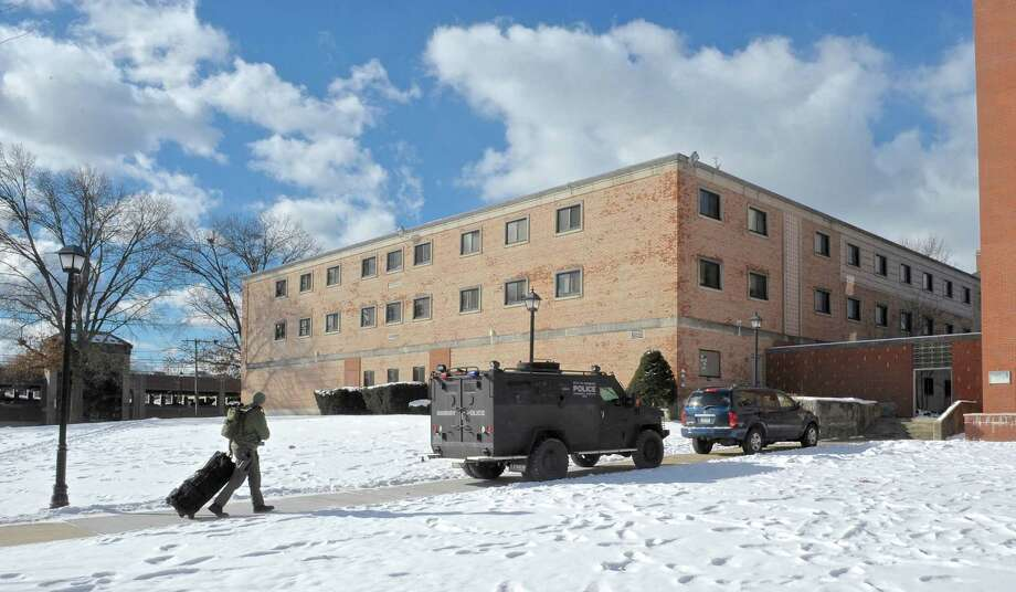 A member of the Newtown Police Department walks past a  Danbury Police Department Emergency Services Unit on their way to a Western Connecticut State University Police Department live shooting exercise with area police departments at the WCSU midtown campus on Thursday, February 11, 2016, in Danbury, Conn. The training drill took place in the university's Litchfield Hall dormitory building. Photo: H John Voorhees III / Hearst Connecticut Media / The News-Times