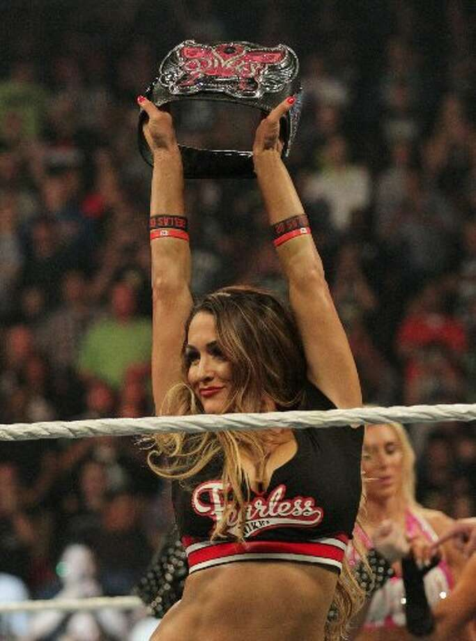 Nikki Bella holds up her Divas Championship belt before the match in which she lost it to Charlotte, at the WWE Night of Champions in September 2015 in Houston. Photo: John Shapley / Houston Chronicle