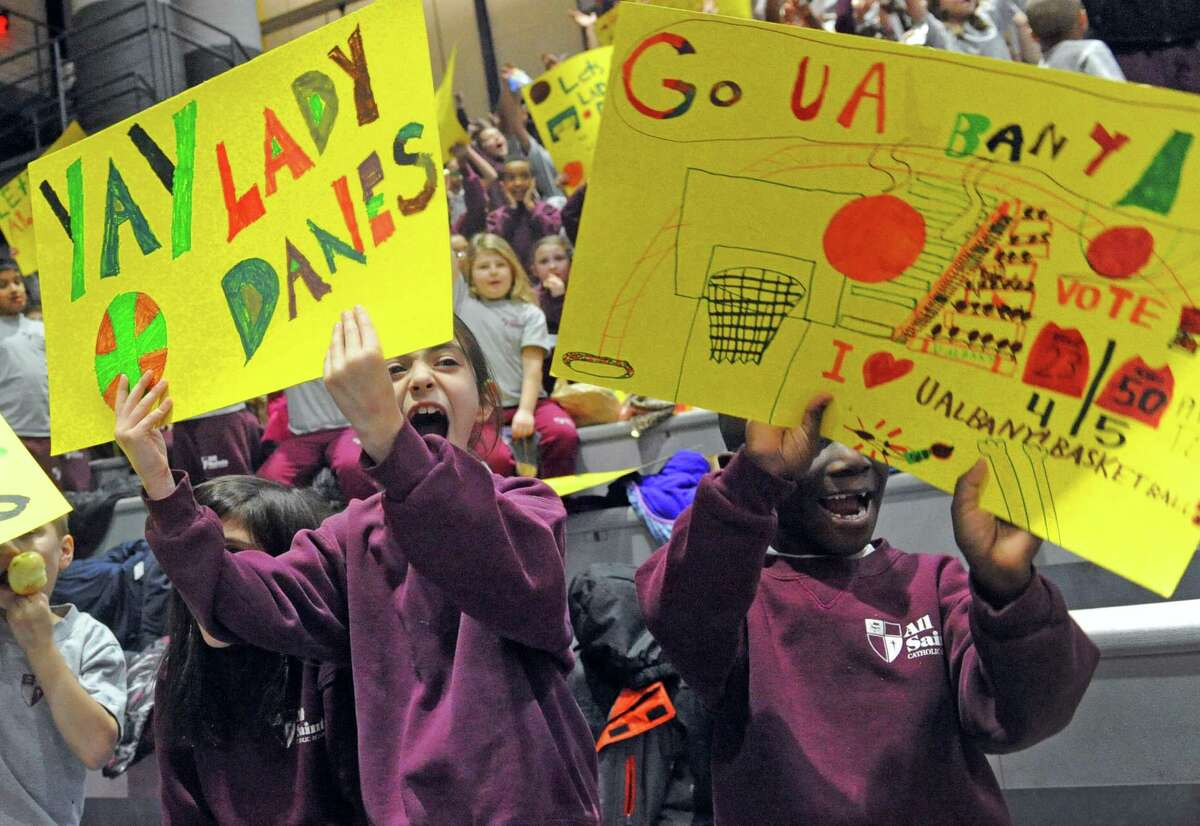All Saints Catholic Academy students Alessandro Marando, left, and Isaiah Osei cheer on the Lady Danes as they play a college women's basketball game against New Hampshire at the SEFCU Arena on Thursday Feb. 10, 2016 in Albany, N.Y. (Michael P. Farrell/Times Union)