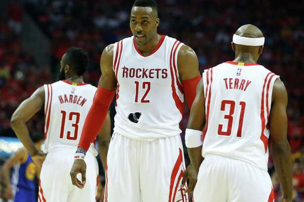 Houston Rockets center Dwight Howard (12) walks up the court past guards James Harden (13) and Jason Terry (31) with a torn jersey during the second quarter of Game 4 of the NBA Western Conference finals against the Golden State Warriors at the Toyota Center on Monday, May 25, 2015, in Houston.  ( James Nielsen / Houston Chronicle )