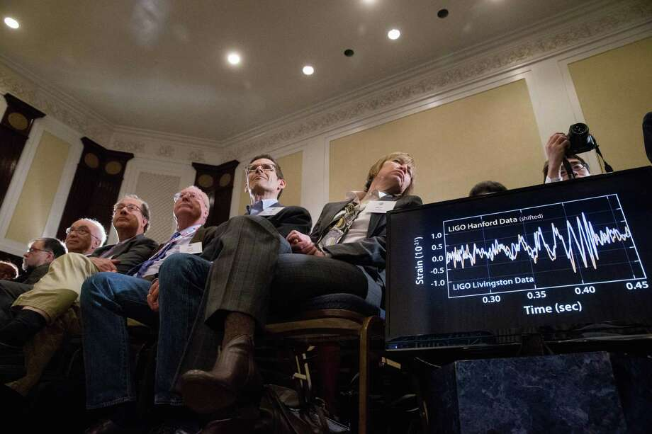 Audience members look at monitors displaying detected data which scientists say is proof of gravitational ripples, Thursday, Feb. 11, 2016, during a news conference at the National Press Club in Washington, just as Albert Einstein predicted a century ago. (AP Photo/Andrew Harnik) Photo: Andrew Harnik, STF / Associated Press / AP
